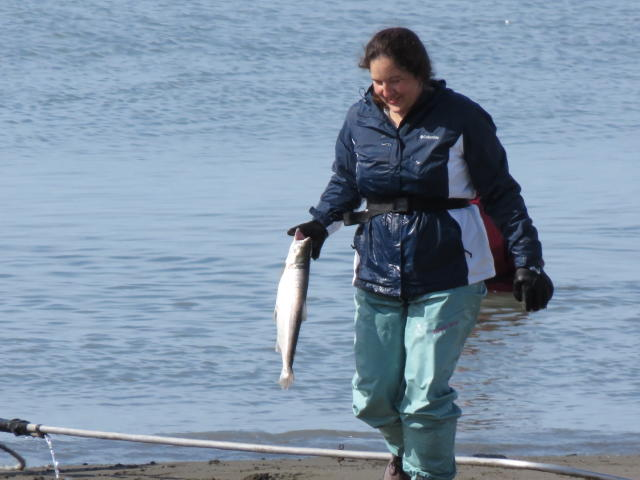 A woman proudly carries her freshly caught fish